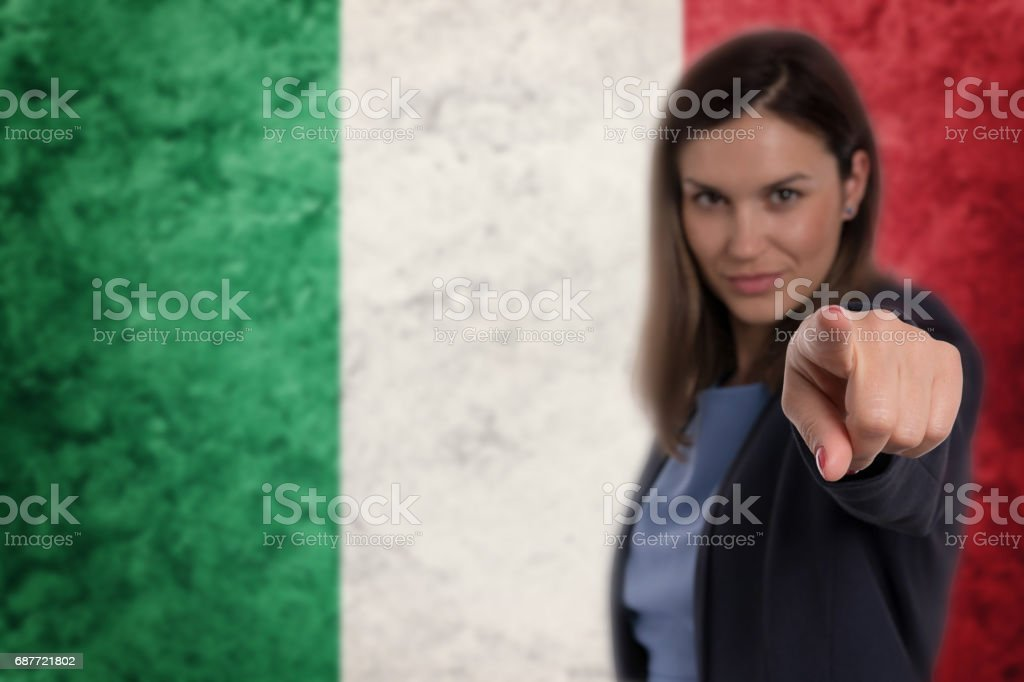 Beautiful businesswoman pointing her finger at you Italian flag background. stock photo