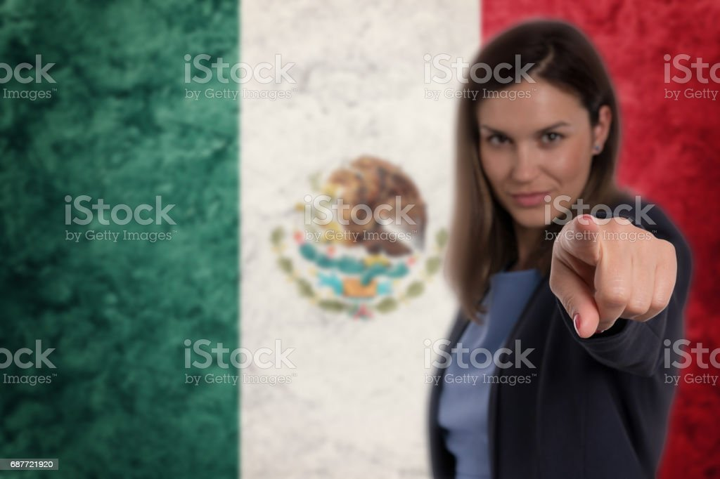 Beautiful businesswoman pointing her finger at you Mexican flag background. stock photo