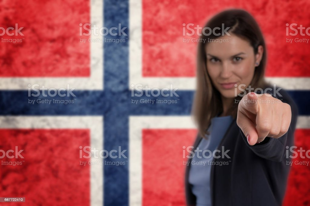 Beautiful businesswoman pointing her finger at you Norwegian flag background. stock photo