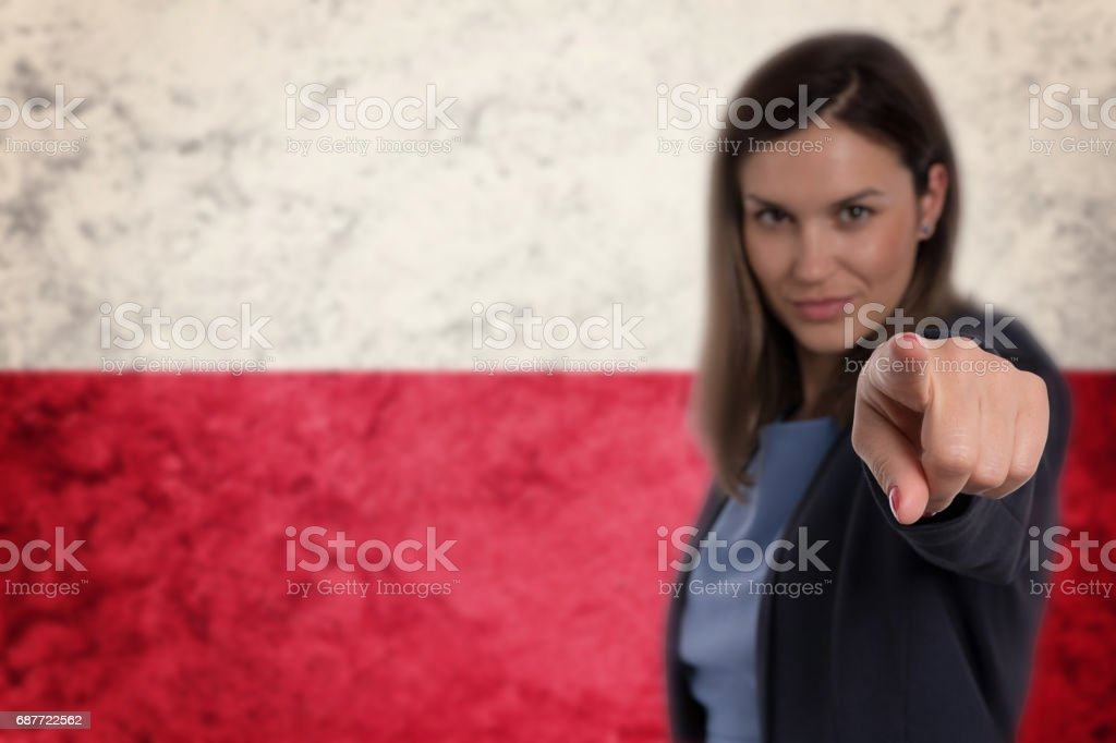 Beautiful businesswoman pointing her finger at you Polish flag background. stock photo