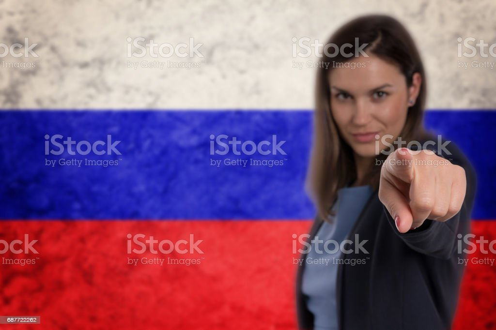 Beautiful businesswoman pointing her finger at you Russian flag background. stock photo