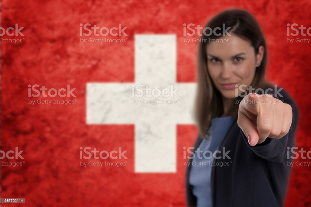 Beautiful businesswoman pointing her finger at you Swiss flag background. stock photo