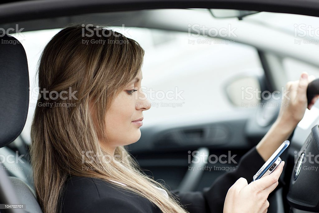 Beautiful businesswoman sending a text while driving royalty-free stock photo