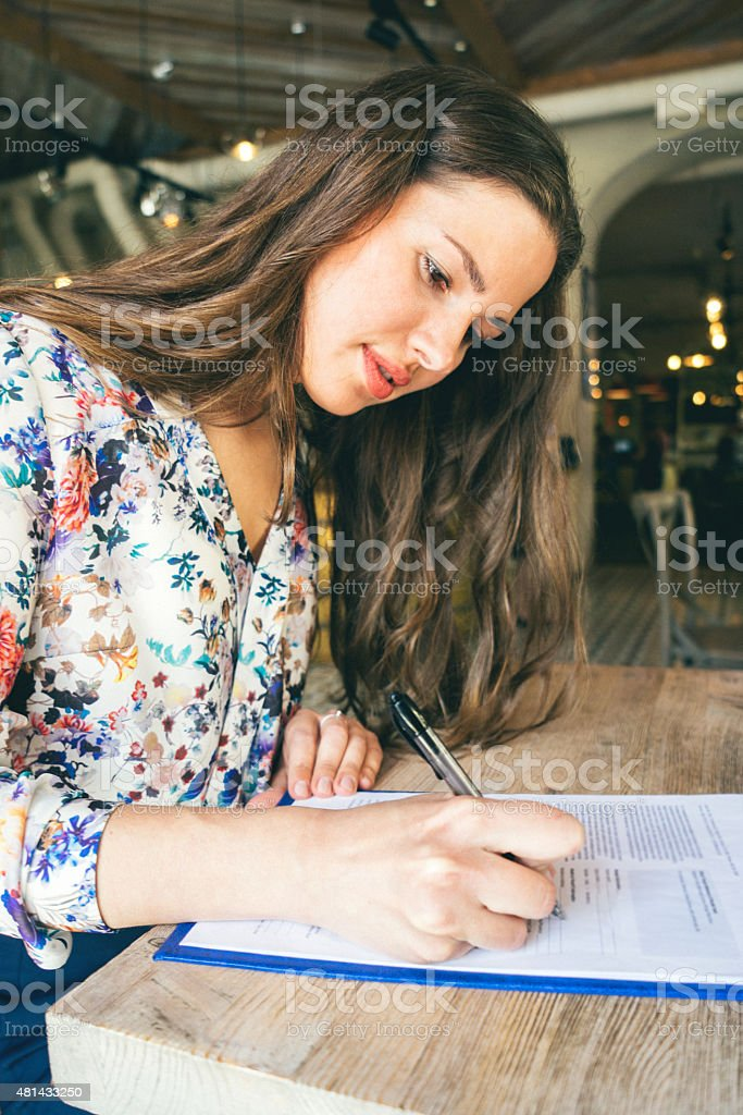Beautiful Businesswoman Signing Contract In A Cafe Indoors stock photo
