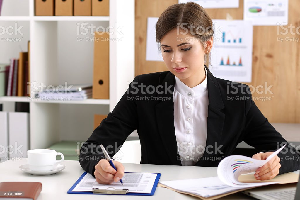 Beautiful businesswoman sit at workplace in office stock photo