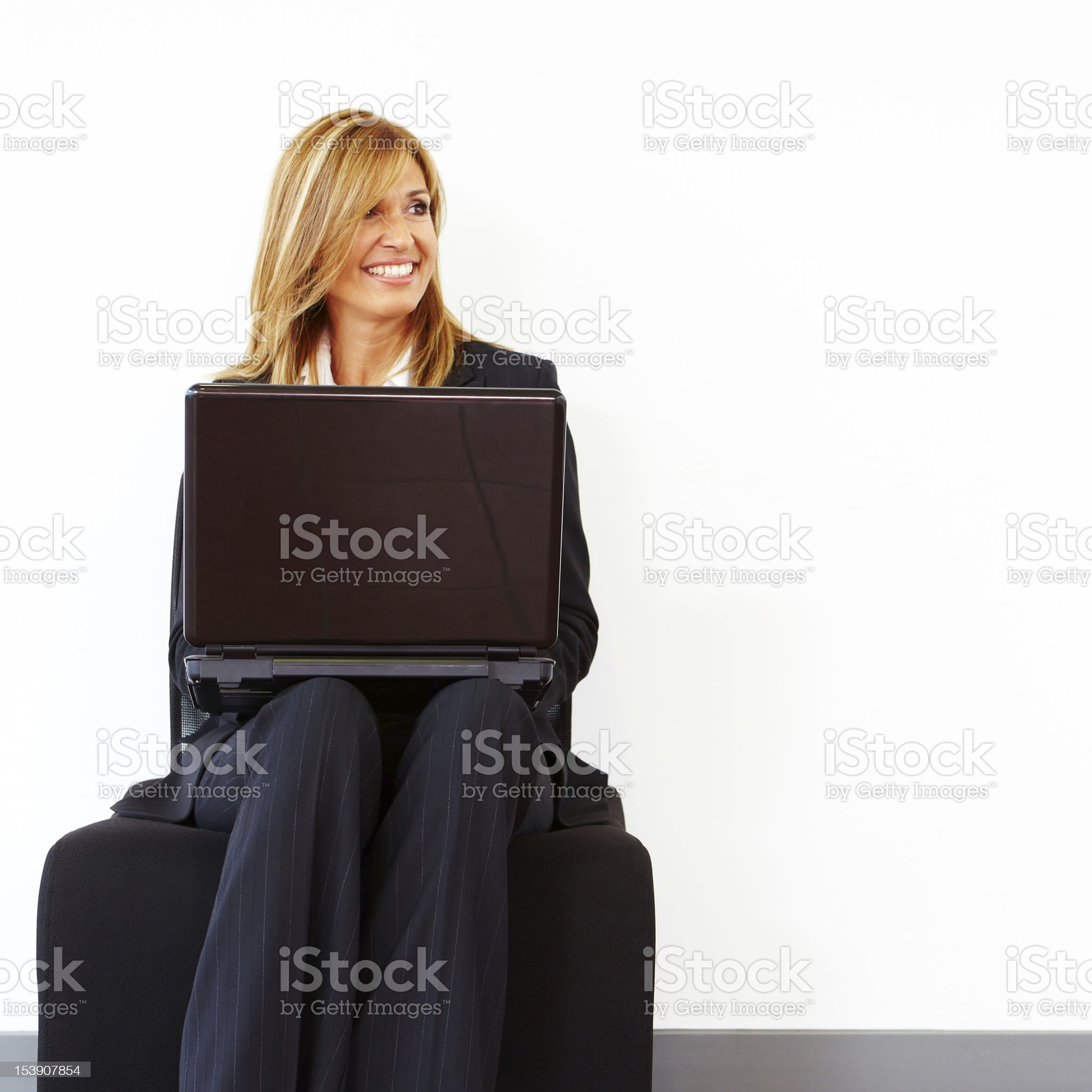 Beautiful businesswoman sitting in chair while working on laptop royalty-free stock photo