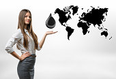 Beautiful businesswoman standing with big oil drop above her open