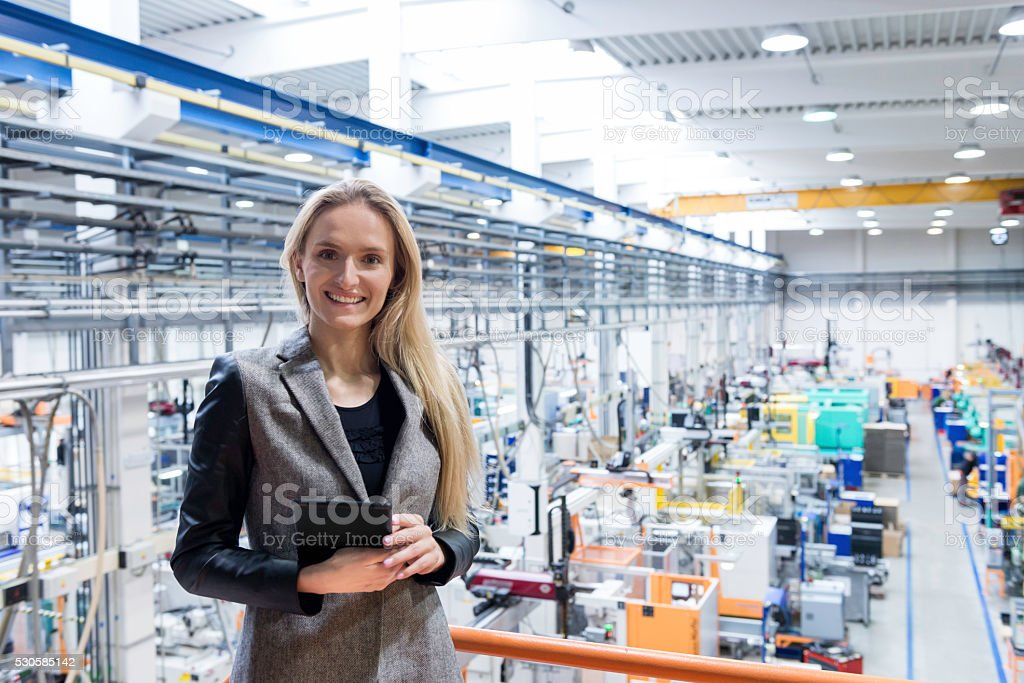 Beautiful businesswoman with tablet in factory stock photo