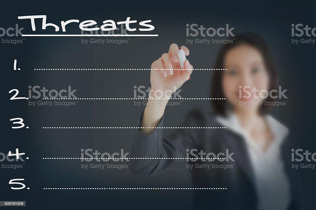 Beautiful businesswoman writing list of business threats stock photo