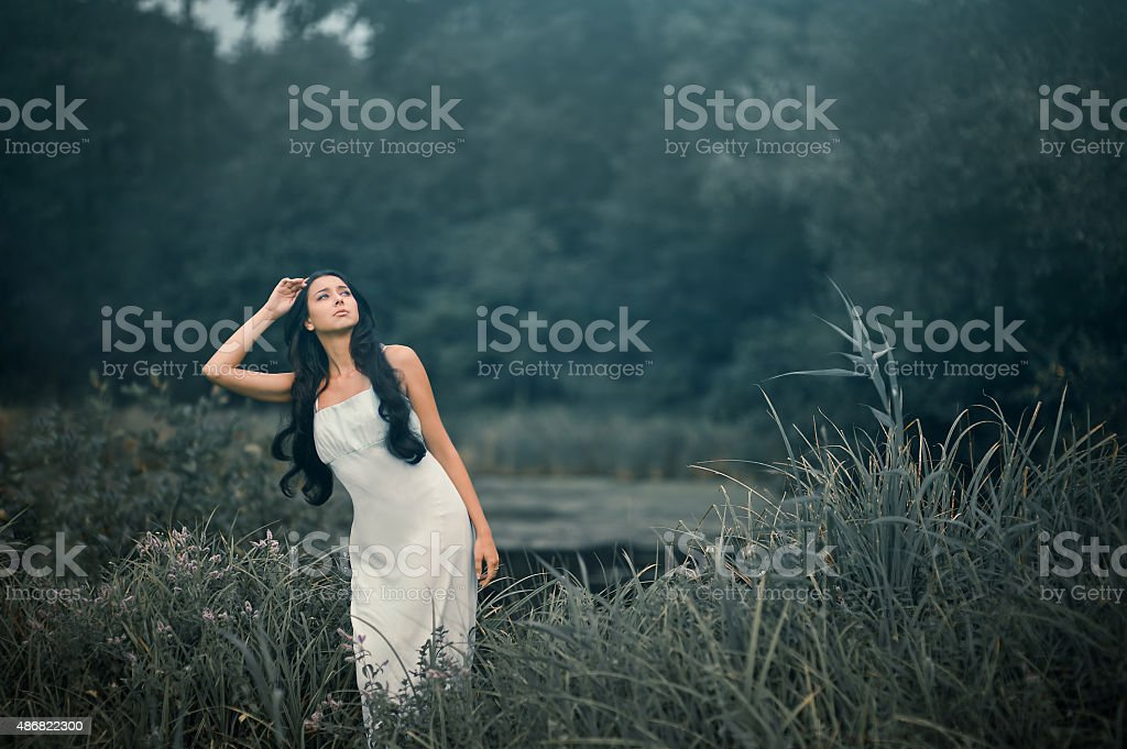 Beautiful but sad woman in fairytale, wood nymph among tall stock photo