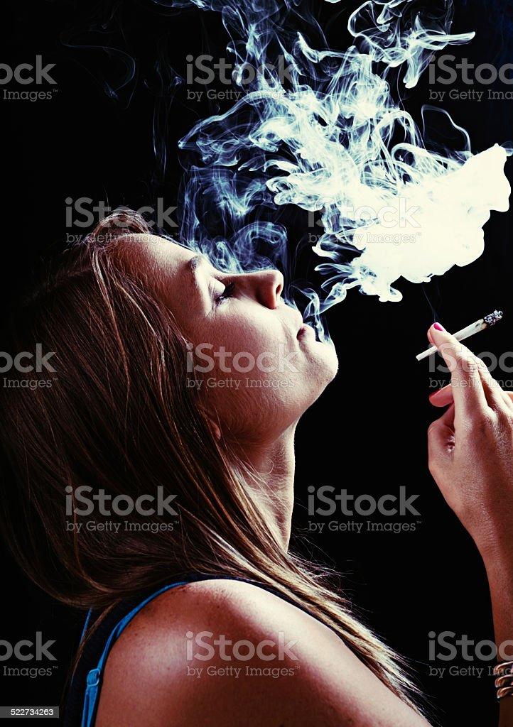 Beautiful but stoned blonde puffing on marijuana reefer stock photo