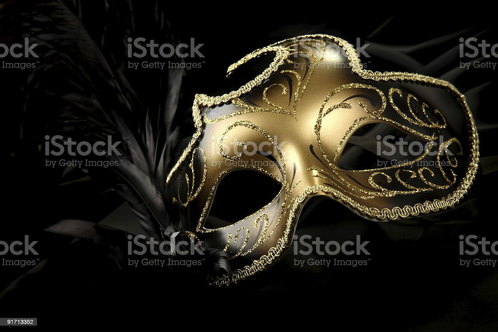 A beautiful carnival mask with black feather and gold decor stock photo