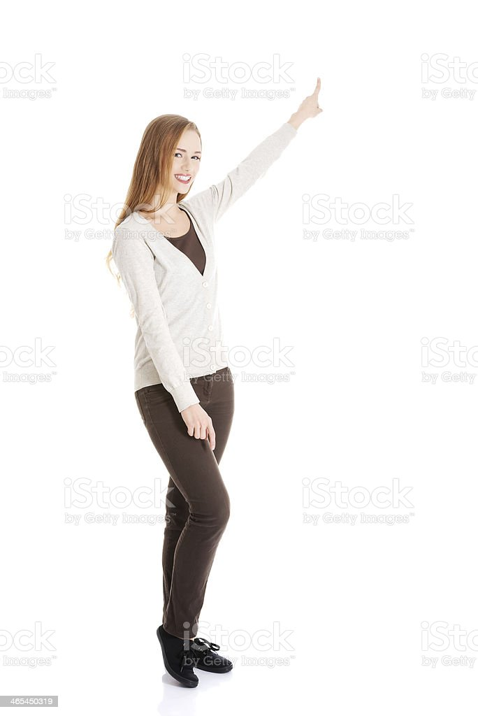 Beautiful casual woman pointing up and advertising. royalty-free stock photo