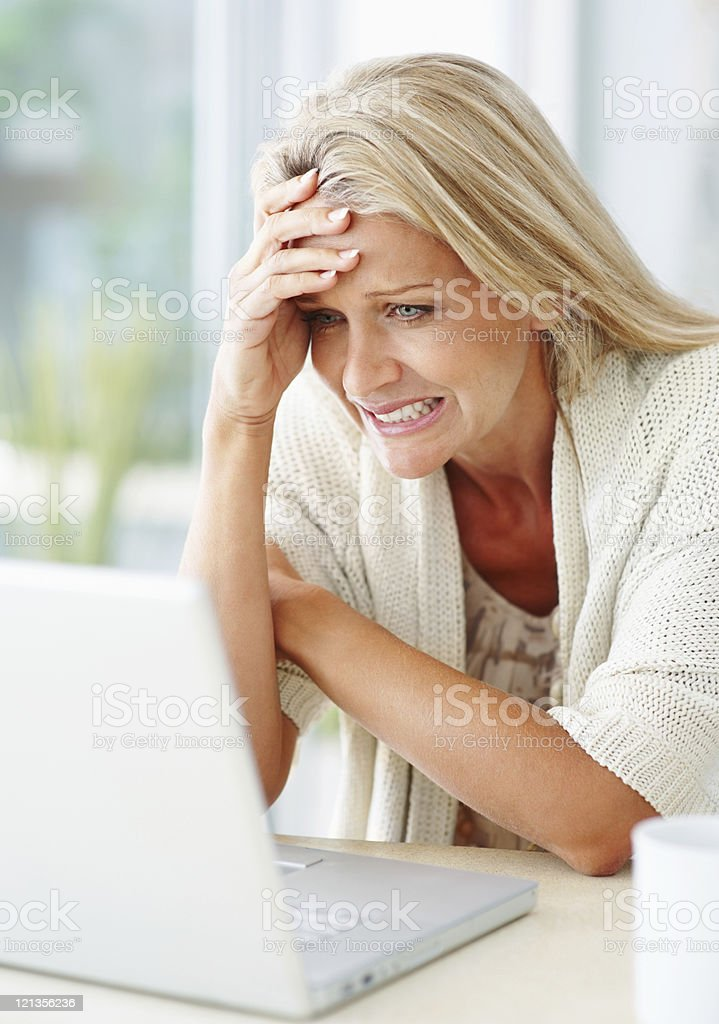 Beautiful casual woman reading bad news on laptop royalty-free stock photo