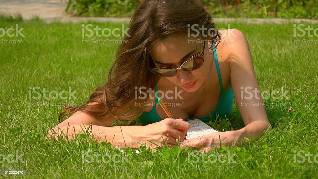 Beautiful caucasian brunette girl laying on the lawn and colorizing stock photo
