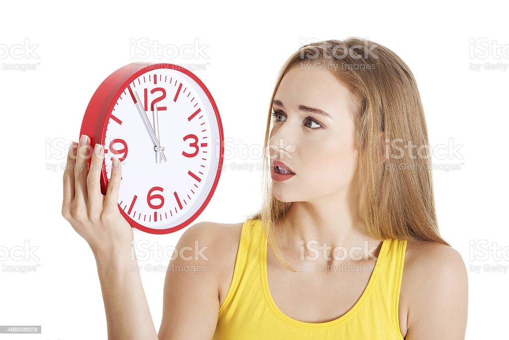 Beautiful caucasian casual woman holding red clock. stock photo