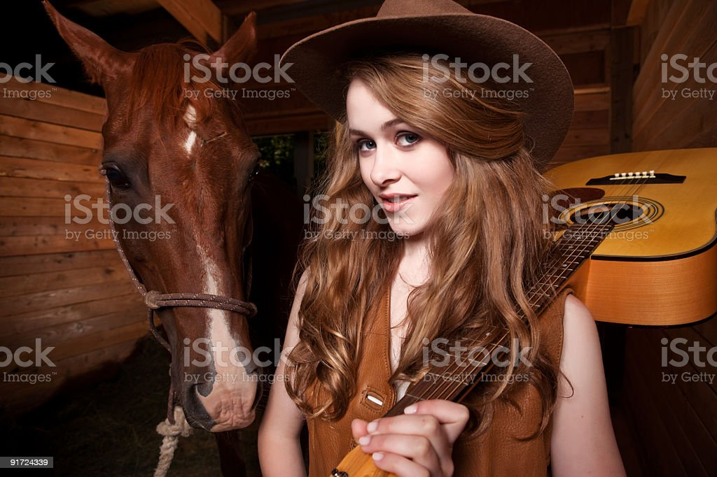 Beautiful caucasian cowgirl with a horse royalty-free stock photo