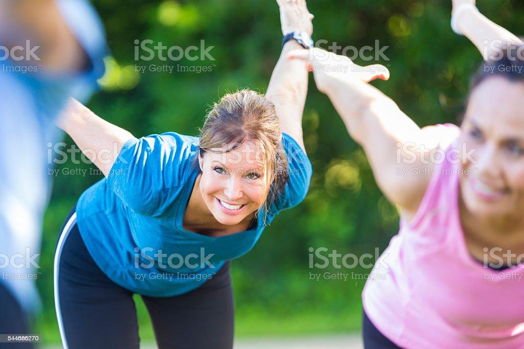 Beautiful Caucasian senior woman in outdoor yoga class stock photo