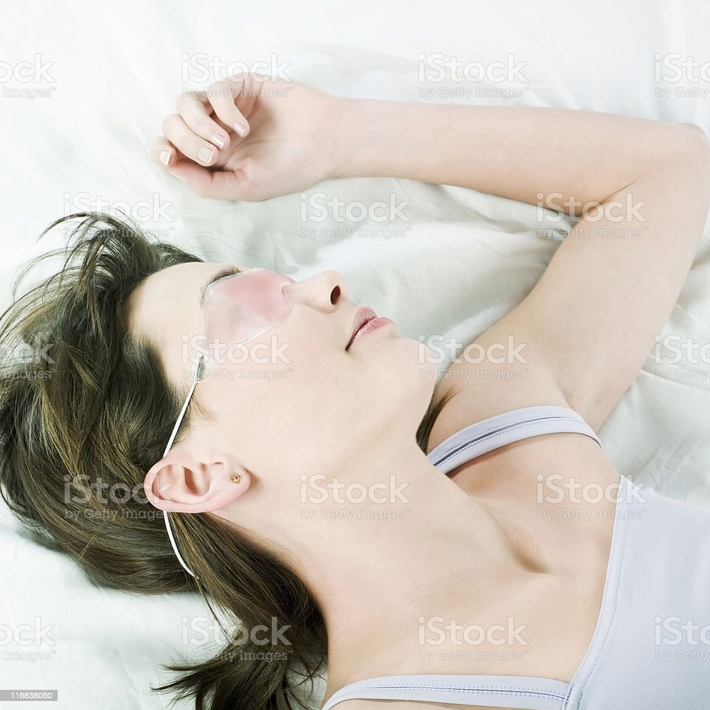 beautiful caucasian woman in bed sleeping wearing a cryogenic mask royalty-free stock photo