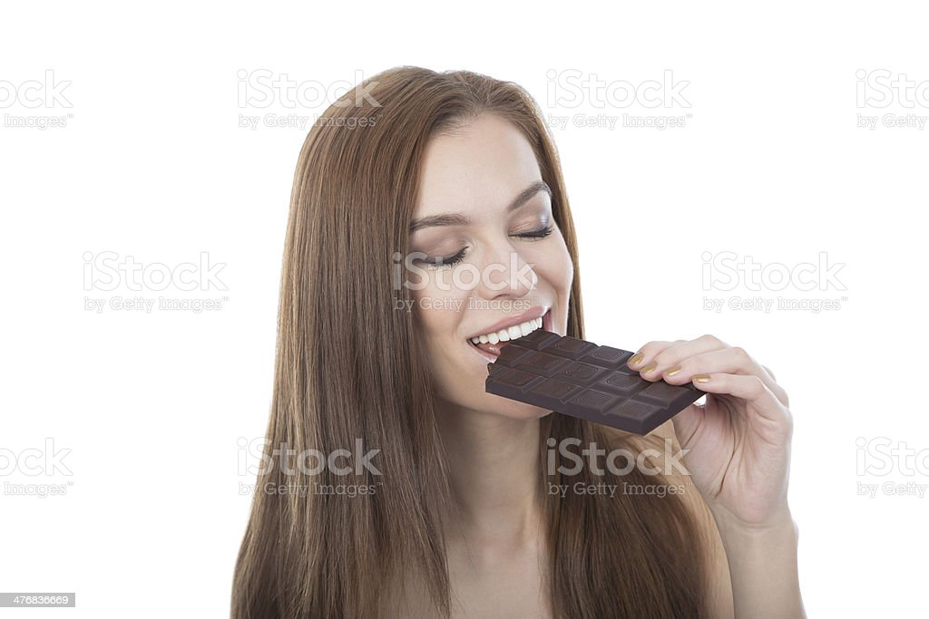 Beautiful caucasian young woman eating a chocolate bar. royalty-free stock photo