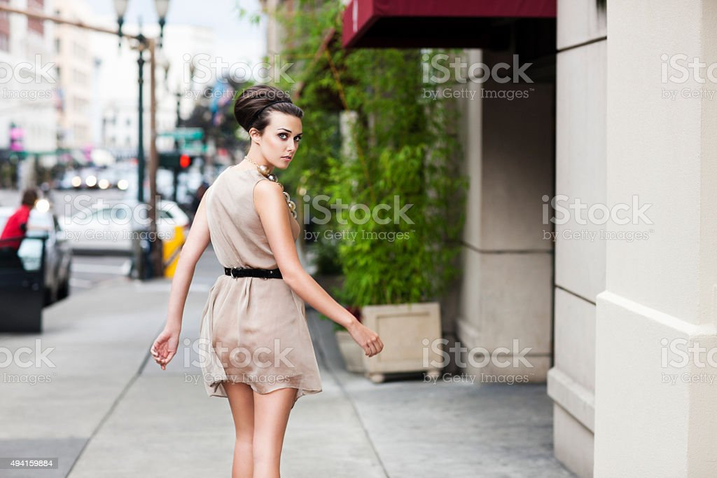Beautiful Caucasian Young Woman Fashion Model Walking on Downtown Sidewalk stock photo