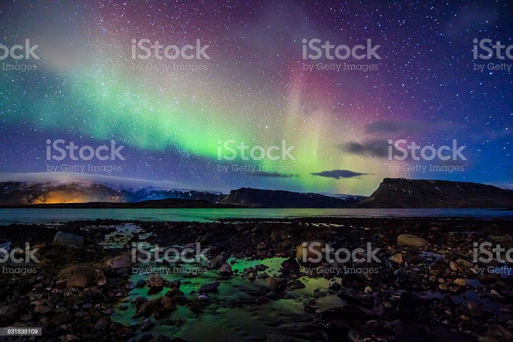 Beautiful celestial Aurora Borealis in Iceland's winter sky near waterstream stock photo