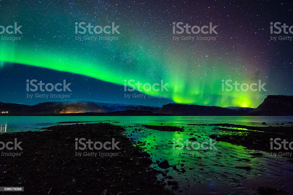 Beautiful celestial Aurora Borealis in Iceland's winter sky near waterstream stock photo