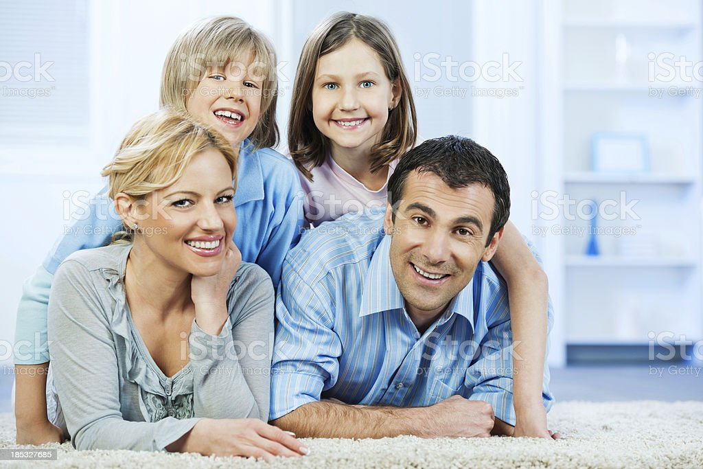 Beautiful cheerful family  laying down on a carpet. royalty-free stock photo