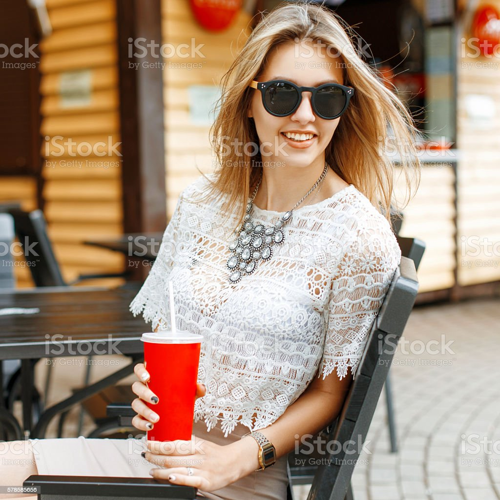 Beautiful cheerful girl with a cute smile drinking a drink stock photo