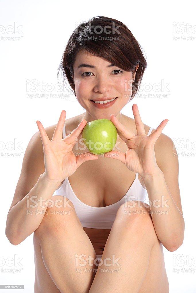 Beautiful cheerful Japanese girl holding ripe green apple fruit royalty-free stock photo