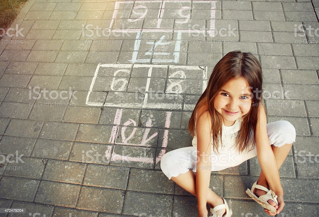 beautiful cheerful little girl playing hopscotch on playground stock photo