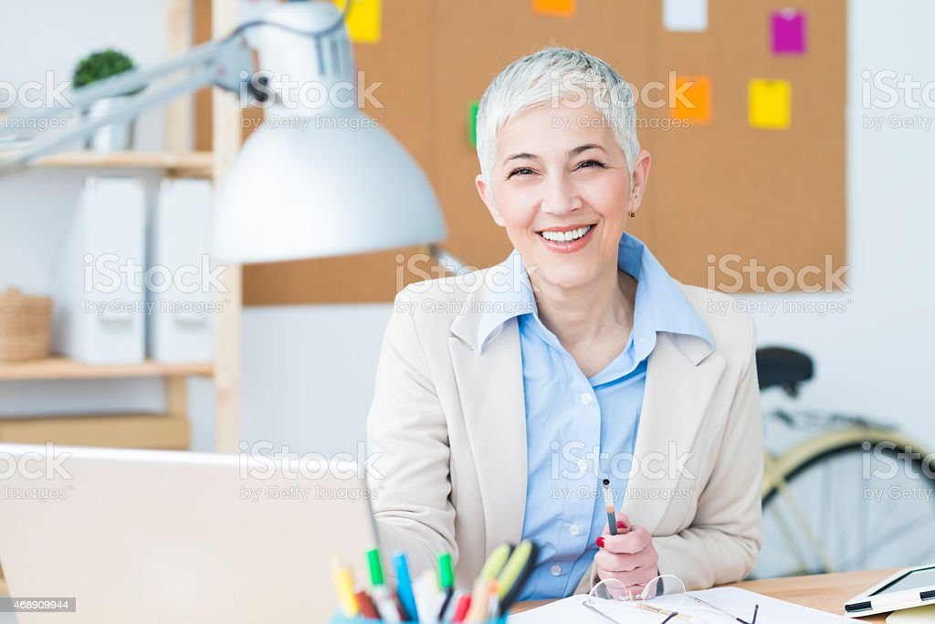 Beautiful cheerful mature woman at office working on computer stock photo