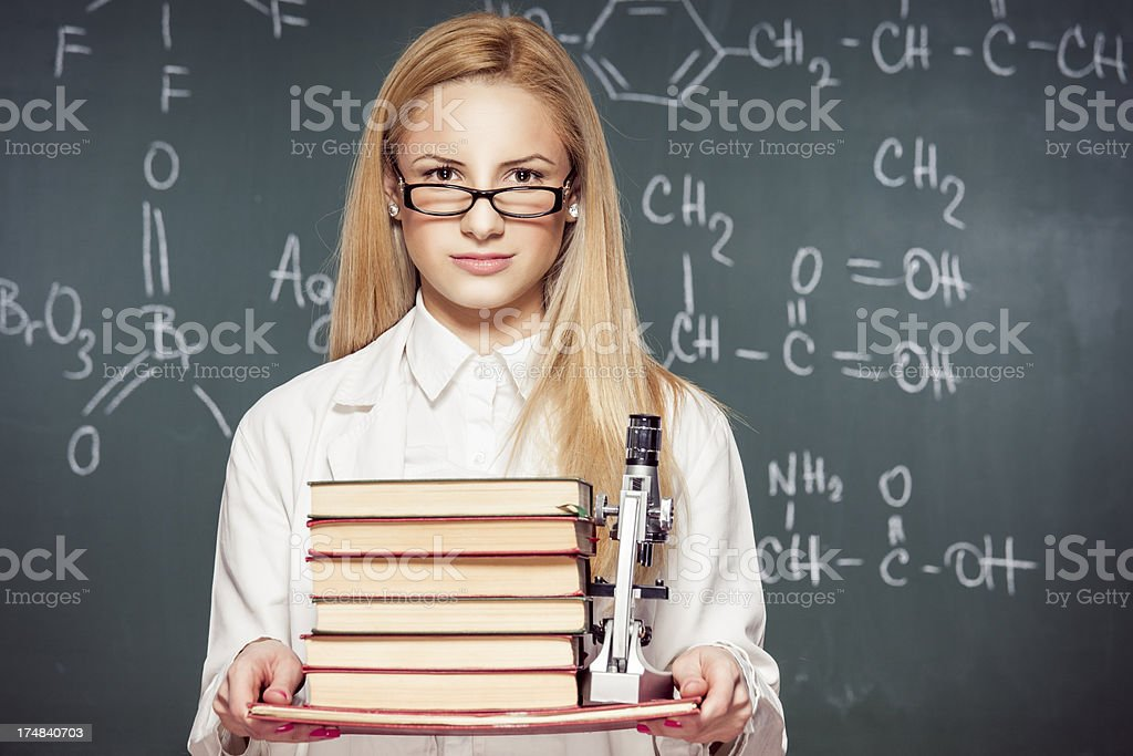 Beautiful Chemistry teacher in front of chalkboard royalty-free stock photo