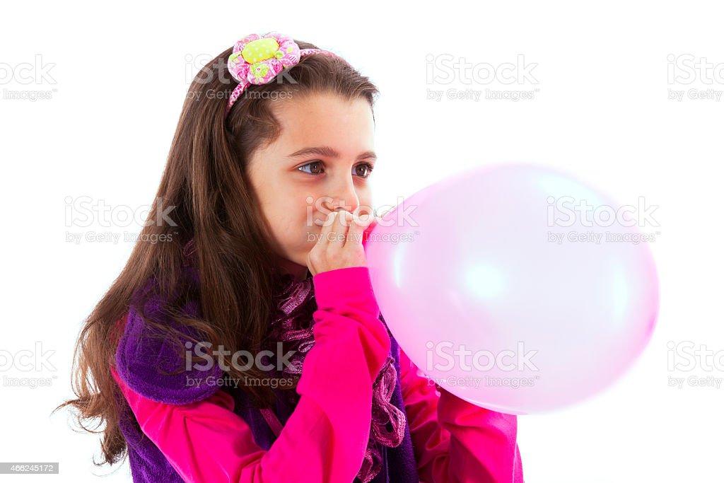 Beautiful child blowing a balloon stock photo
