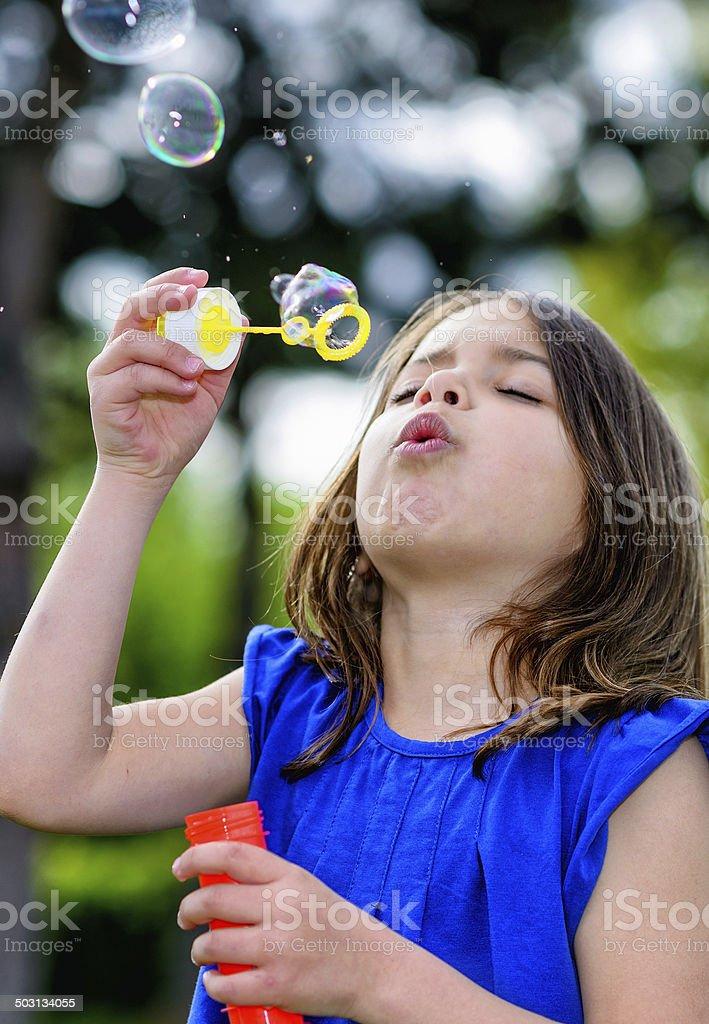beautiful child blowing bubbles royalty-free stock photo