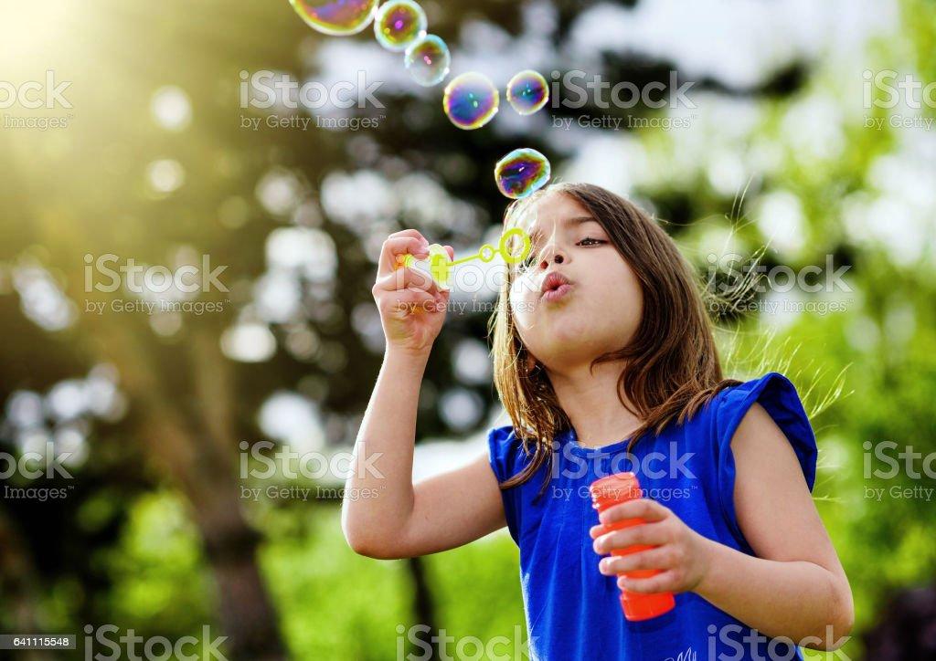 beautiful child blowing bubbles stock photo