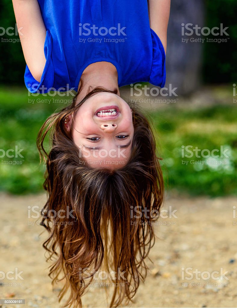 beautiful child hanging upside and laughing royalty-free stock photo