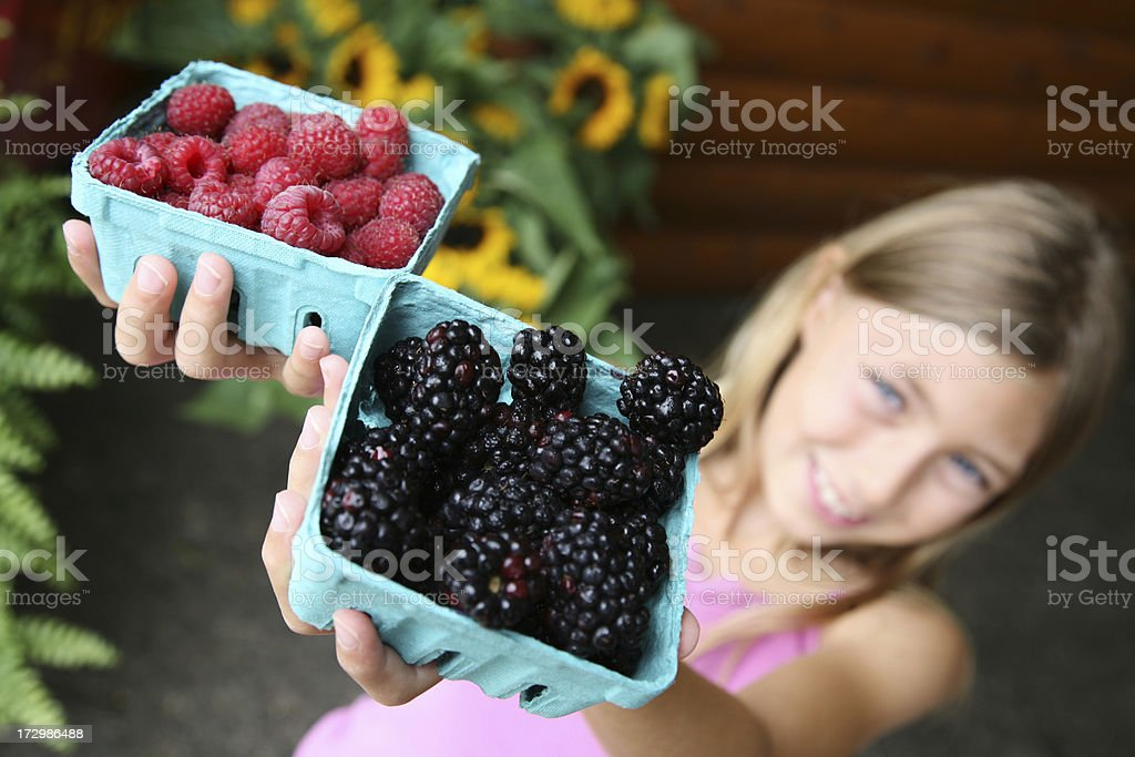Beautiful child holds fresh produce at farmers market stock photo