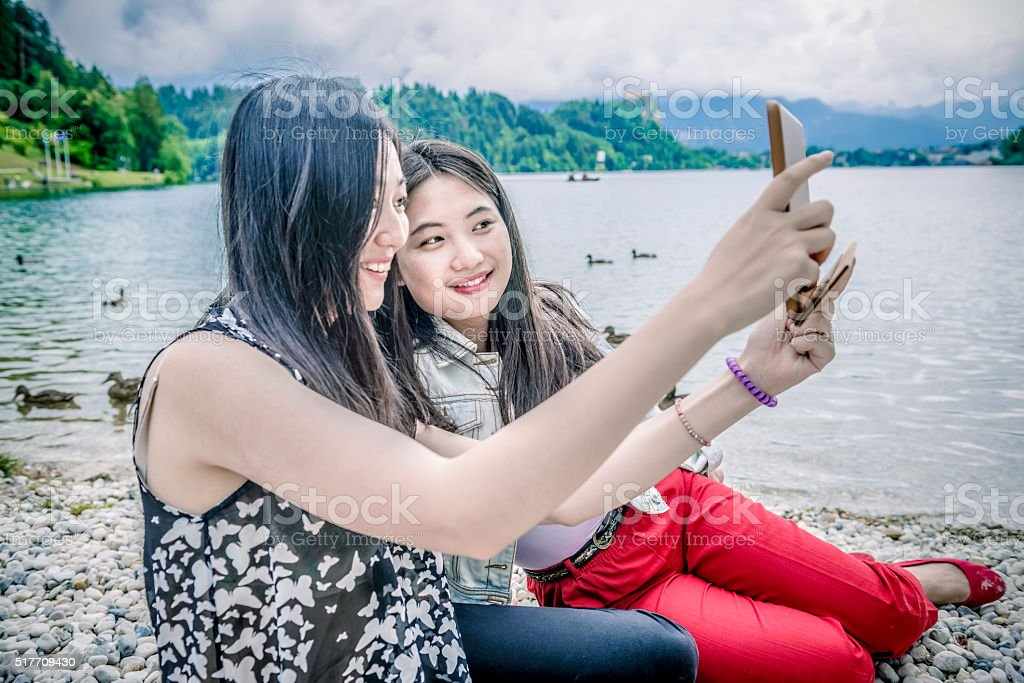 Beautiful Chinese Friends Taking Selfie by Bled Lake, Slovenia, Europe stock photo