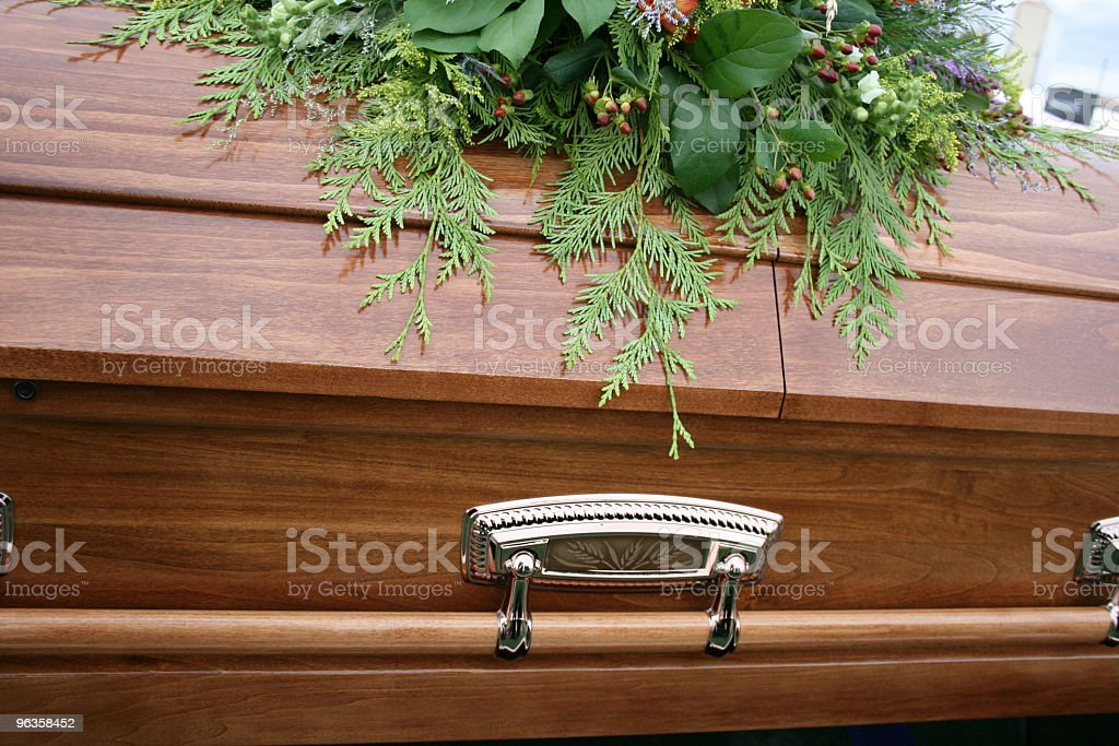 Beautiful closed wooden coffin with plant arrangement on top stock photo