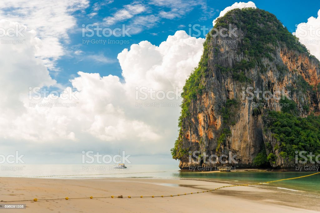Beautiful clouds, high cliff and a small yacht in the sea, Thailand stock photo