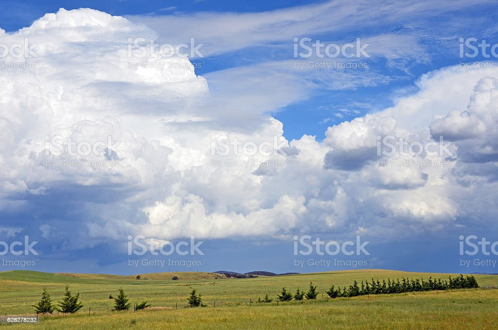 Beautiful cloudscape over rolling green hills and farmland stock photo