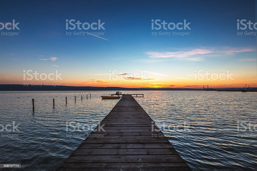 Beautiful cloudscape over the lake and blured boat stock photo