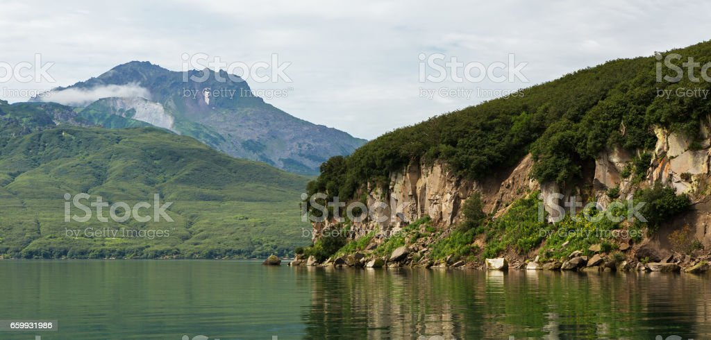Beautiful coast of Kurile Lake is reflected in the water stock photo