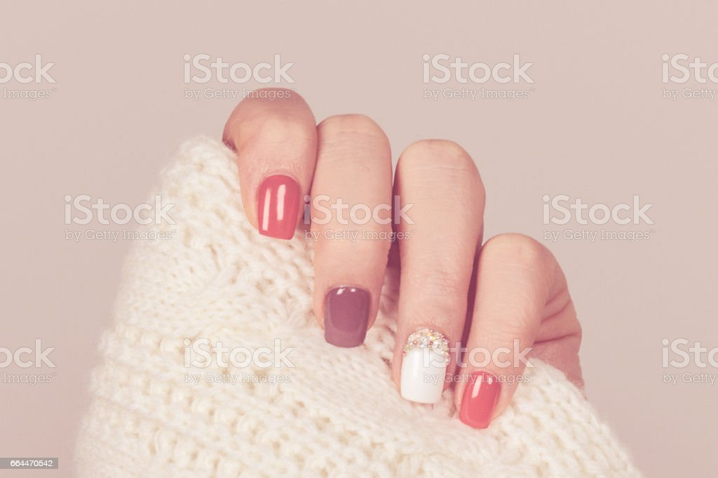 Beautiful colored pastel colors nail polish on hand, closeup. Nail art manicure concept stock photo