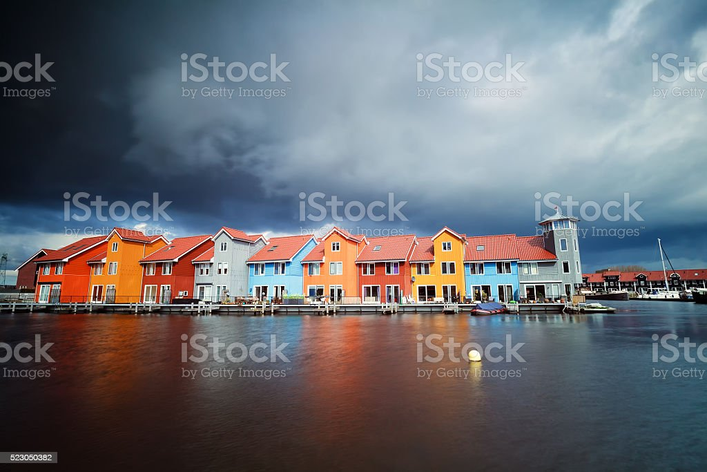 beautiful colorful buildings on water at storm stock photo