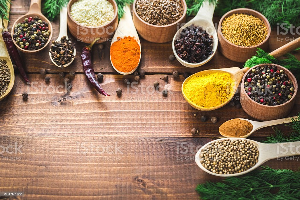 Beautiful colorful spices in wooden spoons and bowls stock photo
