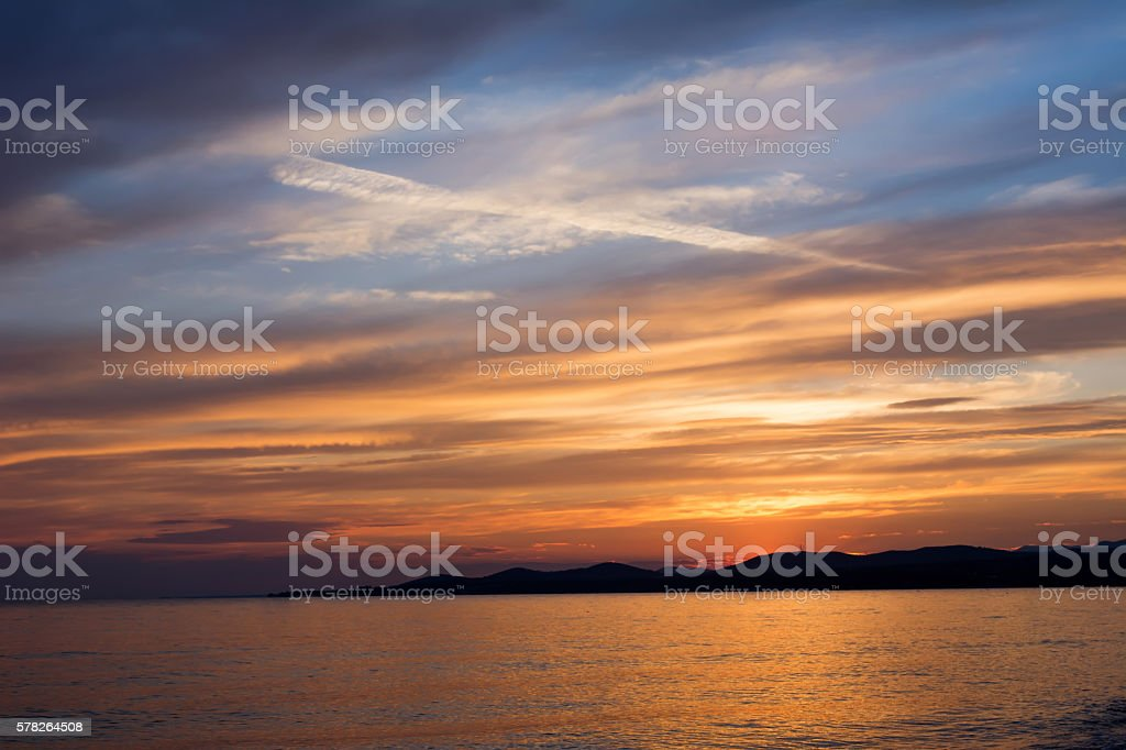 Beautiful colors at sunset with vapor trails on the sky stock photo