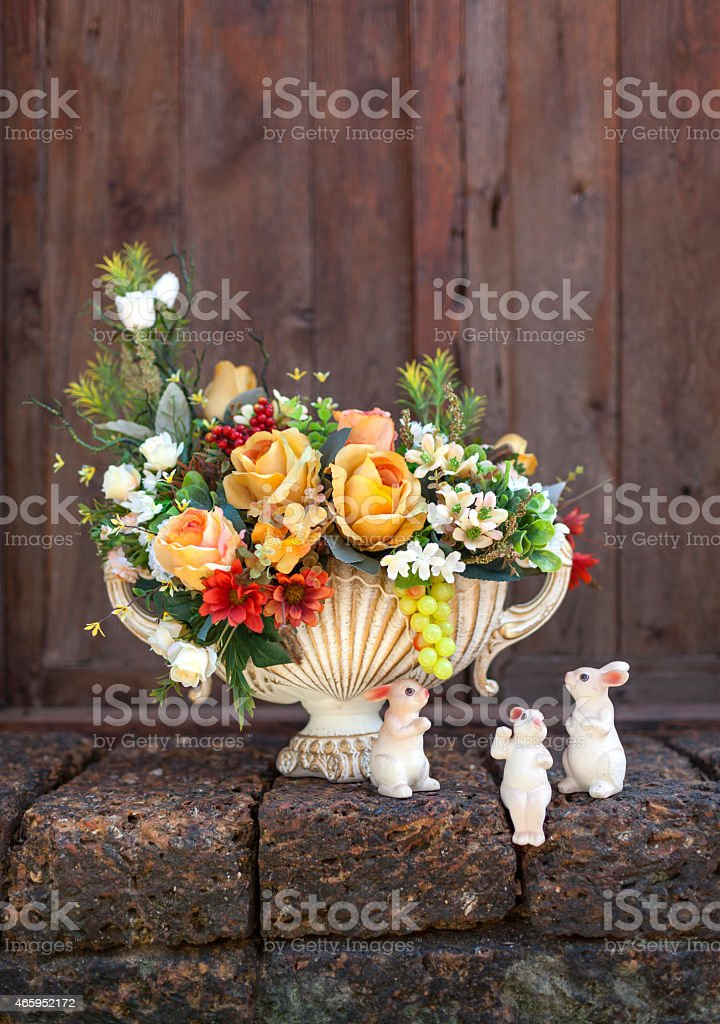 Beautiful colourful flower vase with ceramic rabbits royalty-free stock photo