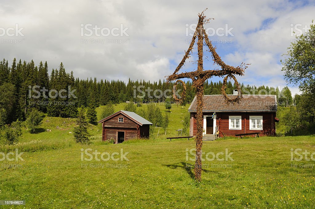 Beautiful cottage and barn with maypole in northern Sweden stock photo
